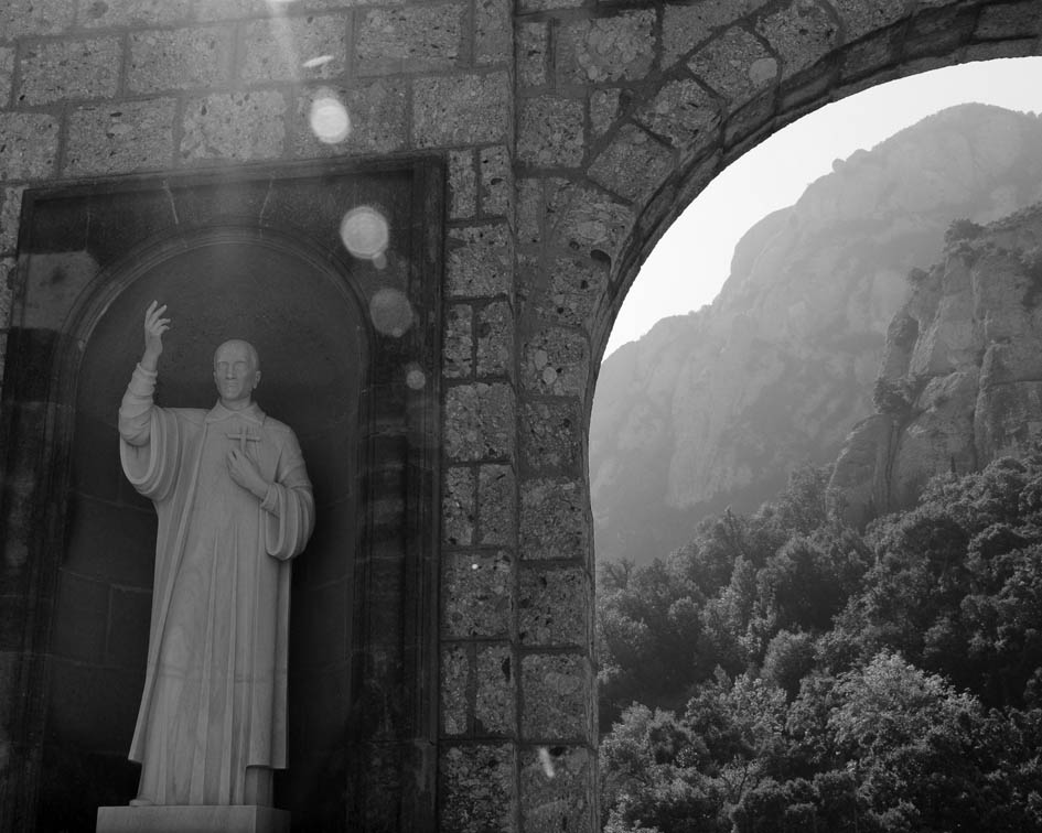 Photo of statue of saint with mountain in background